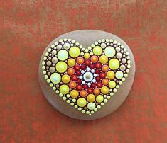 I sell this beautiful hand-painted mandala stone in the colors red, orange, yellow, gold and white. The natural stone from the Danish North Sea coast was painted by hand with acrylic paint in point technique and then sealed with acrylic clear coat. The stone is intended for indoor use