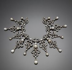 A Victorian diamond and pearl necklace, the graduated diamond and pearl set open scroll links suspend from stylised diamond set palmettes. Set in silver and gold. Diamond set knife edge section. Although there is no frame, the necklace probably had the function of being worn as a tiara.