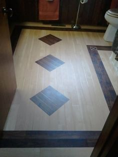 A new bathroom floor using Karndean luxury vinyl tile in contrasting wood tones with custom inserts.