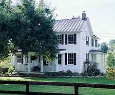 This two-story Colonial farmhouse may look like the all-American home on the outside, but inside a white palette, painted furniture, and repurposed antiques in every room give the home a decidedly European look./