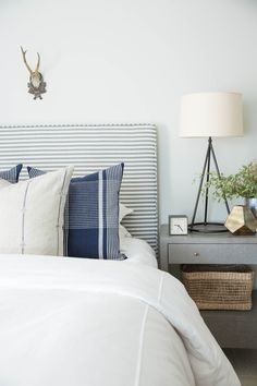 love this neutral modern bedroom with that striped upholstered headboard and those beautiful plaid pillows