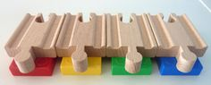 Set of 4: red, blue, green, yellow.  Use these adapters to combine Duplo and your wooden train tracks to make hills, bridges, mountains etc. The adapters hold the track and the Duplo /Lego together without slipping and collapsing. The adapter consists of one short wooden track and one piece of Duplo. Duplo and LEGO are also compatible so you can also build higher tracks using Lego too. We ship the Duplo brick and wooden track as separate pieces not glued together to reduce the shipping cost…