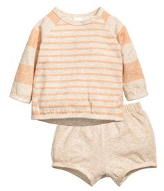 Beige/apricot. BABY EXCLUSIVE/CONSCIOUS. Set in soft, double-knit, organic cotton jersey. Top with buttons at front and long raglan sleeves. Shorts with