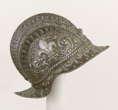 Italian Burgonet, c.1545-47. Thought to have been made for the guard of Pier Luigi Farnese (1503–1547), who ruled as duke of Parma and Piacenza from 1545 to 1547. The raised fleur-de-lis on either side refers to the Farnese coat of arms (six blue fleurs-de-lis on a gold ground). The Metropolitan Museum collection