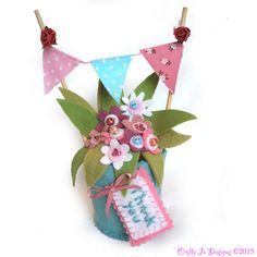 Personalized flower pots make unique thank you gift. This pink felt flower arrangement with tiny bunting will sit on a mantelpiece or shelf for