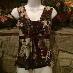 VINTAGE LA KOLAKI BROWN FLORAL GLITTERY TOP VERY PRETTY VINTAGE FLORAL TOP ADORNED WITH BABY BLUE GLITTER BROWN  BUILT IN CAMI LIL JACKET TIES WITH BROWN RIBBON IN FRONT BACK IS ALL FLORAL. IN NEW CONDITION . 92% POLYESTER 7% SPANDEX  THANK YOU FOR VISITING MY CLOSET  LA KOHAKI Tops Blouses