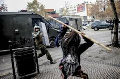 A student clashes with riot police during a demonstration against the government demanding for changes in the state education system in Santiago, June 10, 2014. Chilean students have been protesting against, what they say is, profiteering in the state education system.