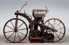 """In November 1885, Gottlieb Daimler installed a smaller version of an engine in a wooden bicycle, creating the first motorcycle (Patent 36-423impff & Sohn """"Vehicle with gas or petroleum drive machine""""). It was named the Reitwagen (""""riding car""""). Maybach rode it for three kilometers (two miles) alongside the river Neckar, from Cannstatt to Untertürkheim, reaching 12 kilometres per hour (7 mph)."""