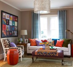 Fabulous fabrics and continuous color give this room a global bazaar feel. Spice hues and jewel box hues, such as curry orange, sapphire, alexandrite, and emerald, add richness to the style. A zebra-stripe chair and a glitzy light fixture provide a youthful oomph, while the colors in the collage of record covers are repeated in the throw pillows and centerpiece items.