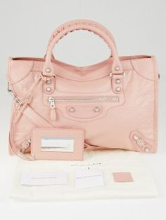 This beautiful Balenciaga Rouge Peche Lambskin Leather Motorcycle City Bag from the 2013 Fall/Winter  (I stamp) has a chic shape that is made of distressed lambskin leather in a nice pale pink color, with gorgeous silver mini giant 12 hardware that creates a lovely color combination.  It also has a detachable shoulder strap for those non-toting days and a matching mirror. A great bag for any stylish fashionista on-the-go.  Current retail price is $1985.