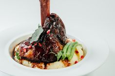 Lamb with pomegranate sauce served with mashed potatoes and herbs