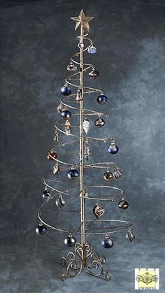 "Ornament Trees - Spiral Wire Ornament Tree - 6 Foot Product ID: 45-0460brd-ornament-tree This beautiful gold spiral ornament tree is the perfect way to display your collection of fine ornaments. Measuring 6 feet tall with a 23"" wide base, it can accommodate up to 75 ornaments. Unique spiral design folds up flat and ""trunk"" disassembles for shipping and storage. The star on top is removable. Please note that additional ship fees may apply on orders of more than one tree. Price: $192.89"