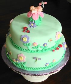 2 tier fondant cake with handmade fondant flowers and baby and gumpaste ladybugs,butterflies and dragonflies. Minus the baby, it would be a lovely birthday cake :)