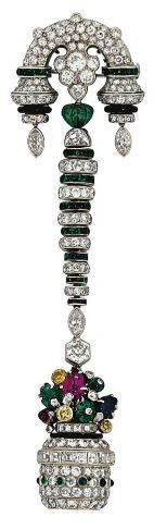 A FINE ART DECO GEM AND DIAMOND LAPEL WATCH. Designed as a brilliant and French-cut diamond, emerald cabochon and black enamel stylised vase, with yellow diamond, carved sapphire, ruby and emerald flower cluster, enclosing a watch with circular silvered dial, black painted Arabic numerals and blued-steel hands, suspended from a graduated buff-top emerald and diamond line and similarly-set arched surmount, mechanical movement, circa 1925, French marks for platinum, numbered.