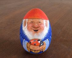 A little gnome holding his pet ladybug. by WoodenEggArt on Etsy, $23.00