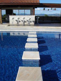 """51 piscinas para curtir o verão - Casa - Com o objetivo de ampliar a área e priorizar a vista da paisagem, a reforma desta piscina foi projetada pela arquiteta Adriana Victorelli, do escritório Neo. A piscina de concreto armado ganhou revestimento de pastilhas Atlas (5 x 5 cm). Uma das bordas é infinita; as outras, são """"peito de pombo"""". A piscina tem 1,5 m de profundidade."""