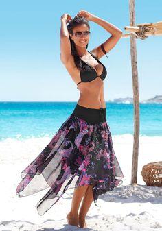 Tolles Strandkleid, das als Rock oder Kleid getragen werden kann. Mit einem unifarbenen, gesmokten Oberteil und einem allover bedruckten, asymmetrischen Rockteil. Leicht transparente Webware.