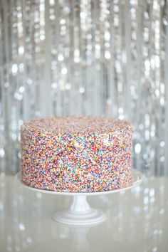 hundreds and thousands cake + silver streamers backdrop | rainbow sprinkles #stylemepretty