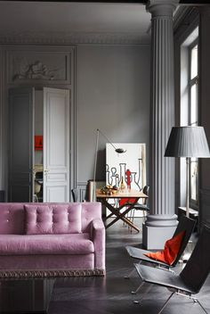 Adore this lavender sofa with the ornate trim with the pale grey walls and column-beautiful.
