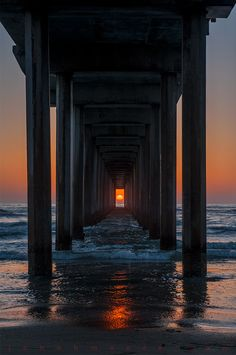 Scripps Pier, La Jolla, California. The sun aligns this way only twice a year. Photo by John H. Moore.