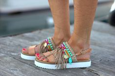 Greek leather sandals handmade to order.  Malibu is a pair of unique genuine leather sandals with anatomic white sole, really comfortable and so hippie chic! Decorated with suede fringes, friendship bracelets and semiprecious stones. They will give a glamorous and boho detail at your outfit that will make the diference!   sizes available EU____.....35......36......37......38.......39.......40......41.......42 U.K.___......2....3-3.5.....4.........5........6........6.5.......7........8…