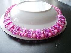 die Kette ist rosa/pink leider ist das Pink nicht so gut zu erkennen. Die großen Perlen sind Katzenaugenperlen. Leuchten im Dunkeln
