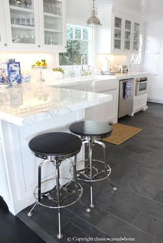 grey flooring White kitchen with grey tile.hmmm, two barstools. If we dont go with an island, I like the idea of a small amount of seating like this to encourage a comfy, hangout kitchen area (not an awkward stand around one) Kitchen Redo, Kitchen Tiles, Kitchen Flooring, New Kitchen, Kitchen Remodel, Kitchen Dining, Kitchen White, Kitchen Layout, Kitchen With Slate Floor