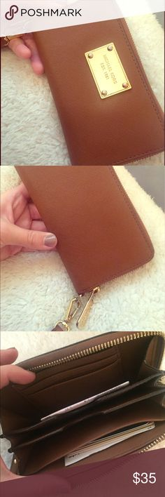 Michael kors wallet Brown mk wallet in great condition. Only a couple scratches on the metal in front. Can fit iPhone in. SHIPPING REDUCED ON FIRST PURCHASE Michael Kors Bags Clutches & Wristlets