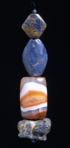 Sumerian beads of lapis lazuli and agate; the bottom amulet is in the shape of a calf. C.2600BC Ur