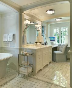 Sweet master bathroom design with freestanding oval tub, marble tiles floor, white single bathroom vanity with marble countertop with drop-down vanity, Waterworks Easton Etagere with Clear Glass, double sconces, TV and blue tufted vanity chair.
