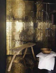 Gold tiles in shower, contrast with weathered timber stool