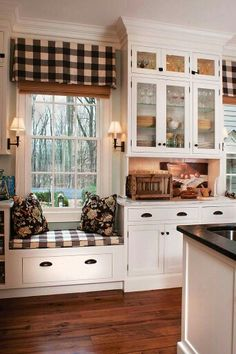 Cream painted kitchen cabinets,  glass doors, iron knobs and pulls, black and white buffalo check fabric.  Wood flooring and slat shade.  Perfection for a updated farmhouse, country space.