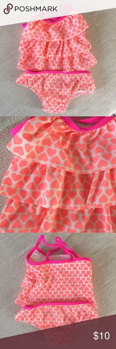 """Carter's Coral Heart Print Tankini Bright and beachy coral heart print on a two-piece tankini. Fun ruffle top with pink cross-cross straps. So cute for the beach or pool this summer! My baby wore this about twice before she got too big for it. Minor pilling on the seat. Great condition! Bundle and save 15%! Just click """"Add to Bundle"""" on ANY two or more of my listings, and a 15% discount will automatically be applied--plus you pay only one shipping fee! Carter's Swim Bikinis"""