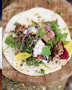 Jamie Oliver's Recipe: ground lamb kebabs with crumbled pistachios on a toasted flat bread, with spring mix and red onion marinated in lemon juice.  Delicious <3