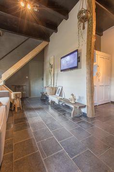Prachtige verouderde natuursteen tegels van Van den Heuvel & Van Duuren. Hier gecombineerd met een schitterende houten keuken.