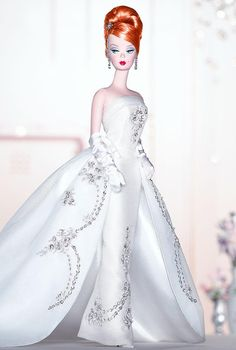 Limited edition redheaded Joyeux™ Barbie® doll ~ FAO Schwarz exclusive. In a dazzling, fitted white satin and organza strapless gown that is clouded over with a dramatic, detachable overskirt. For added shimmer, silvery sequins and faux pearls adorn this snowy-white showstopper. A rhinestone tiara and drop earrings complete the festive mood.