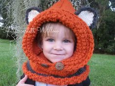 What a sneaky little fox! This adorable hand knit cowl/hood is not only fun but super warm for the coldest of winter days. Easy to slip on and off and loose around the face, very comfortable and soft. Made in a warm orange color accented with a charcoal black/gray, and two wooden buttons.