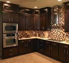 kitchens with dark brown cabinets - Bing Images... I like the glas cabinets and the door pulls
