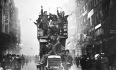 People celebrate the end of war on a London bus