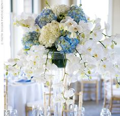 A footed vase filled with hydrangeas, phalaenopsis orchids, and calla lilies topped the head table, while lower arrangements of the same flowers decorated the others
