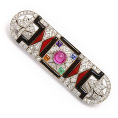 Art Deco diamond and black onyx brooch, set in platinum, the center embellished with a  cabochon-cut natural ruby with an emerald, sapphire, amethyst and citrine in each of the four corners.    French, ca. 1920