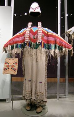 """Yakama Two Hide Dress.    Circa 1890, Washington. With basket hat (1910), purse (1910), necklace (1930) and moccasins (1890.) Dress made of hide, pony beads, faceted """"Russian"""" glass beads, fire polished glass beads, cut glass beads, seed beads and sinew. Hat made of plant material, seed beads and thread. Earrings made of dentallium shell, painted beads and brass hoops. Necklace made of brass beads and leather. Purse made of corn husk, yarn and hide. Moccasins made of hide and sinew."""