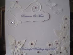 Commissioned wedding card - white on white with a few purple touches/gems - die cut butterflies, flourishes, flowers and label design