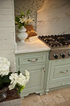 I love the color and style of the cabinets and the white marble countertops are the perfect choice!