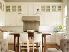 Two industrial light pendants hang over a freestanding dark stained kitchen island lined with Emeco Hudson Barstools.