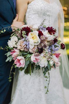 loose, abstract bridal bouquet of white peony, white majolik spray rose, lavender astrantia, burgundy ranunculus, light pink parrot tulip, lavender stock, burgundy dahlia, purple heather, quicksand rose, seeded eucalyptus, ivy & olive leaf.