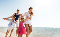 Playful young family on the beach. stock photo