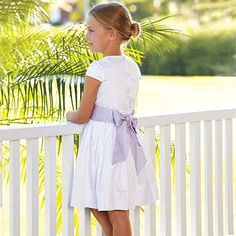 love how the purple sash adds a splash of color to this white party dress....