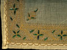 Mat, India, 19th century. 46 x 67 cm. Beetle wings incorporated into a design of stylised flowerrs stitched in laid and couched gold threads and braids.  Gift of Miss C.M. Harris. Photograph by Stephen Brayne.