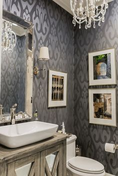 Bathroom with dark gray wallpaper, luxurious chandelier, and rustic cabinet